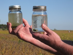 Ohio farmer Jeff Rasawehr, a 2009 SARE grantee, illustrates cover crops' role in protecting water quality. The jar on the right holds runoff from a cover-cropped field; on the left is runoff from a non-cover-cropped field.  Photo credit: Sean McGovern, SARE Outreach